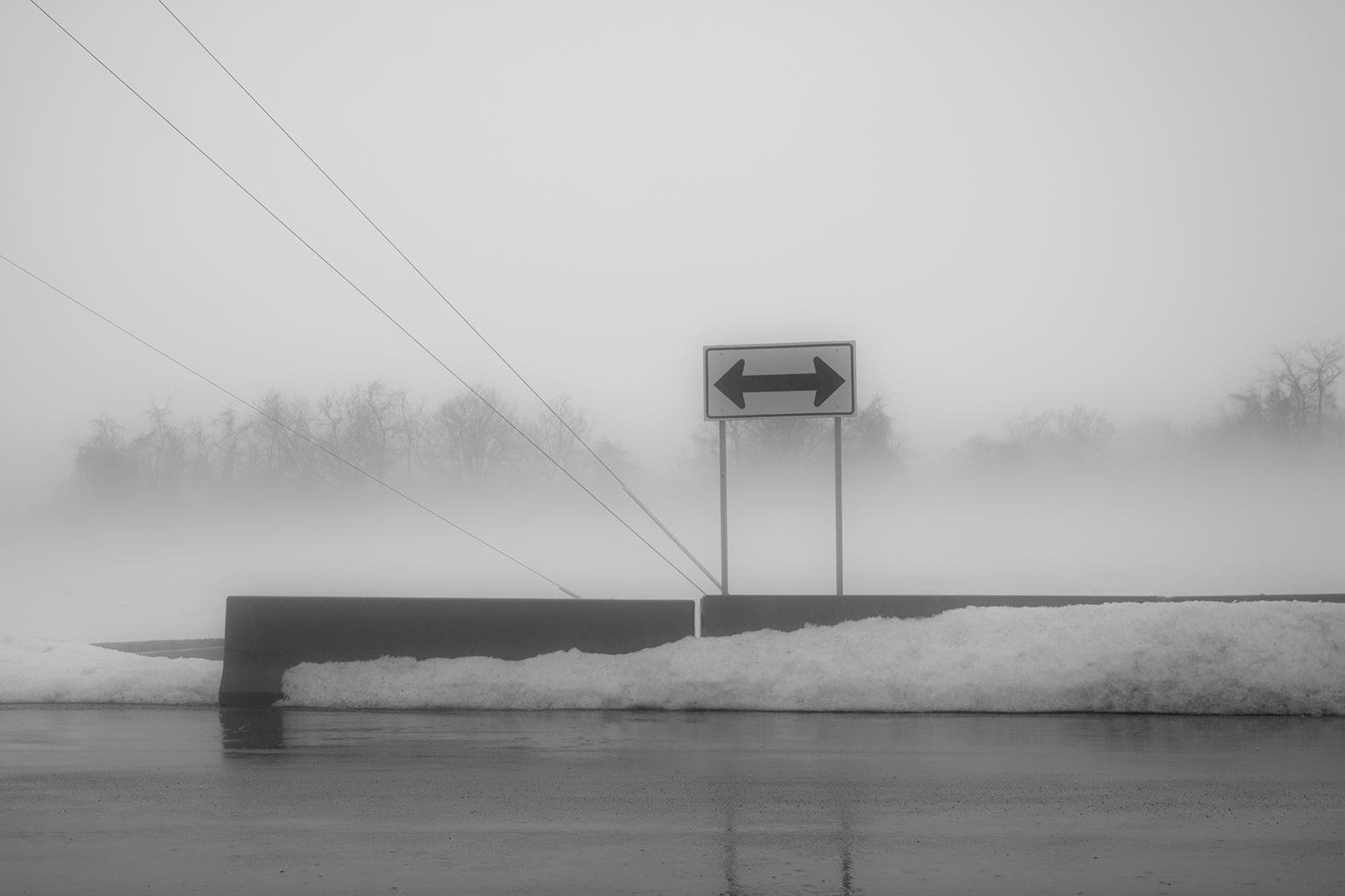 A sign on a foggy snowy day