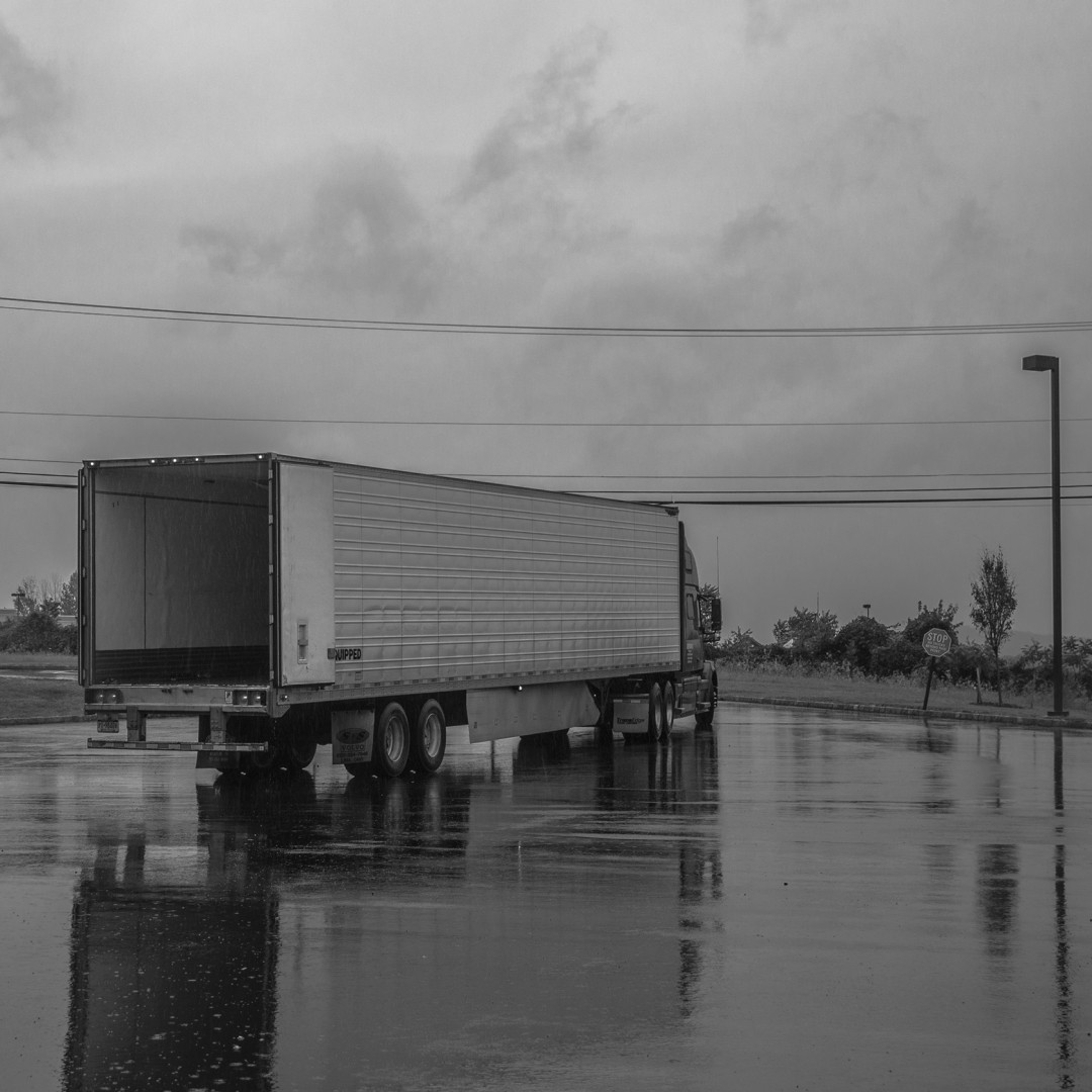 The back of an unloaded truck in the rain