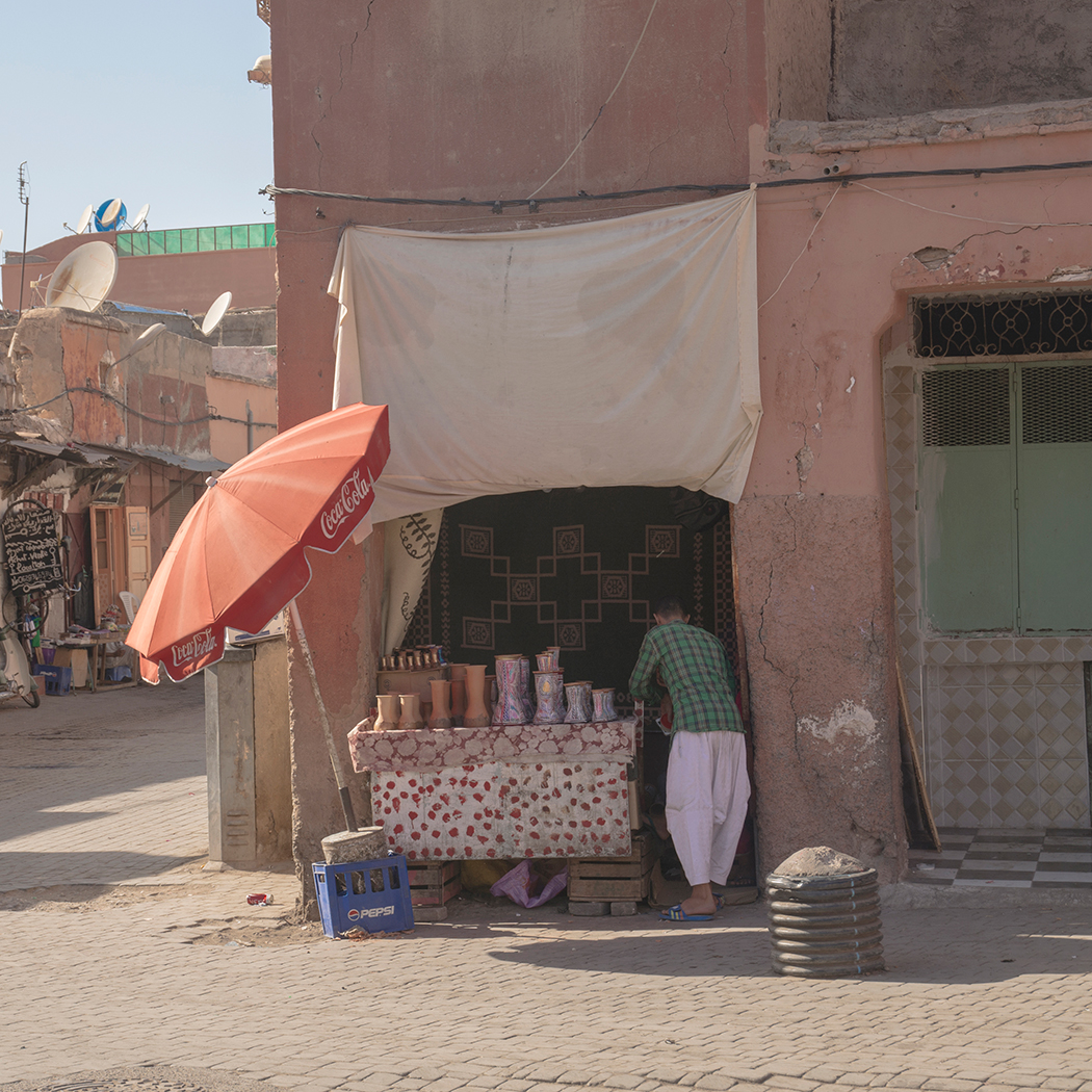 A street vendor in Marrakech selling drums under a Coca Cola Umbrella
