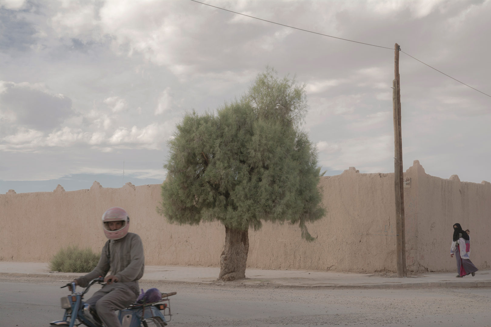 A mother, her baby, a tree and a scooter. Rissani Morocco