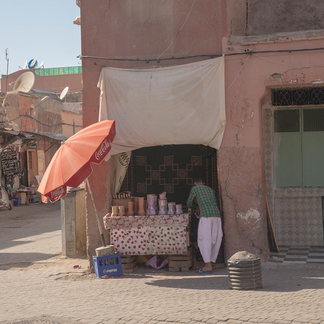 A street vendor in Marrakech selling drums under a Coca Cola Umbrella